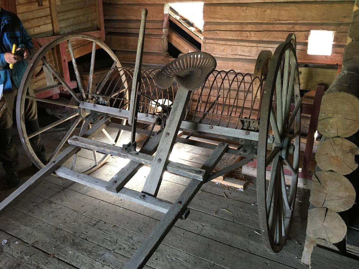 Hestetrukken rive for raking av høy. Fot og håndbetjent mekanisme for løfting av tinder via inngrep i hjulnav. Hjul av tre. Dampbøyd felg med 12 eiker, to felgstykker. Jordbruksredskap til hest hovedsakelig brukt av menn.  Tilstand god