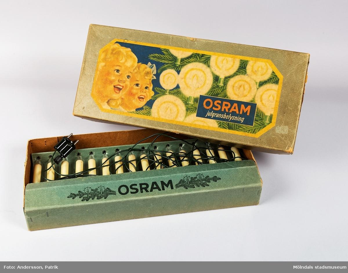 """Julgransbelysning för inomhusbruk i förpackning från 1950-talet, tillverkad av Osram. Belysningen består av 16 st ljus i glas. I förpackningen ligger det även 2 st ljus i reserv. Förpackningen är grön och är av papp. På locket finns en målning med två barnansikten som tittar på en tindrande gran.  Det står också tryckt: """"OSRAM julgransbelysning"""".  Inuti förpackningen finns namnet """"ORSAM"""", tryckt.  Julgransbelysningen härstammar från 1600-talets Tyskland, men det var i slutet av 1800-talet som idén till den elektriska julgransbelysningen föddes. Julen 1882 använde nämligen Edward Hibberd Johnson som var VD för Edison Electric Light Company i New York,  80 st glödlampor i färgerna röd, vit och blå till sin gran för första gången. I New York blev detta ingen succé.  När en tidning i Detroit skrev att Johnsons gran """"var en makalös syn"""" och granens glödlampor var """"stora som en engelsk valnöt"""", så blev det en succé!  Men det var inte förrän runt 1900 som den elektriska julgransbelysning kom ut till försäljning i affärerna. Det var dock bara överklassen som kunde köpa den då eftersom den var dyr i produktion.  I handeln kunde den därför kosta det som idag motsvarar cirka 15000 kr. Det var först under 1930-talet som belysningen fick mer folkliga priser."""