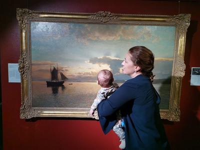 Kvinne med barn på armen står og ser på et maleri.