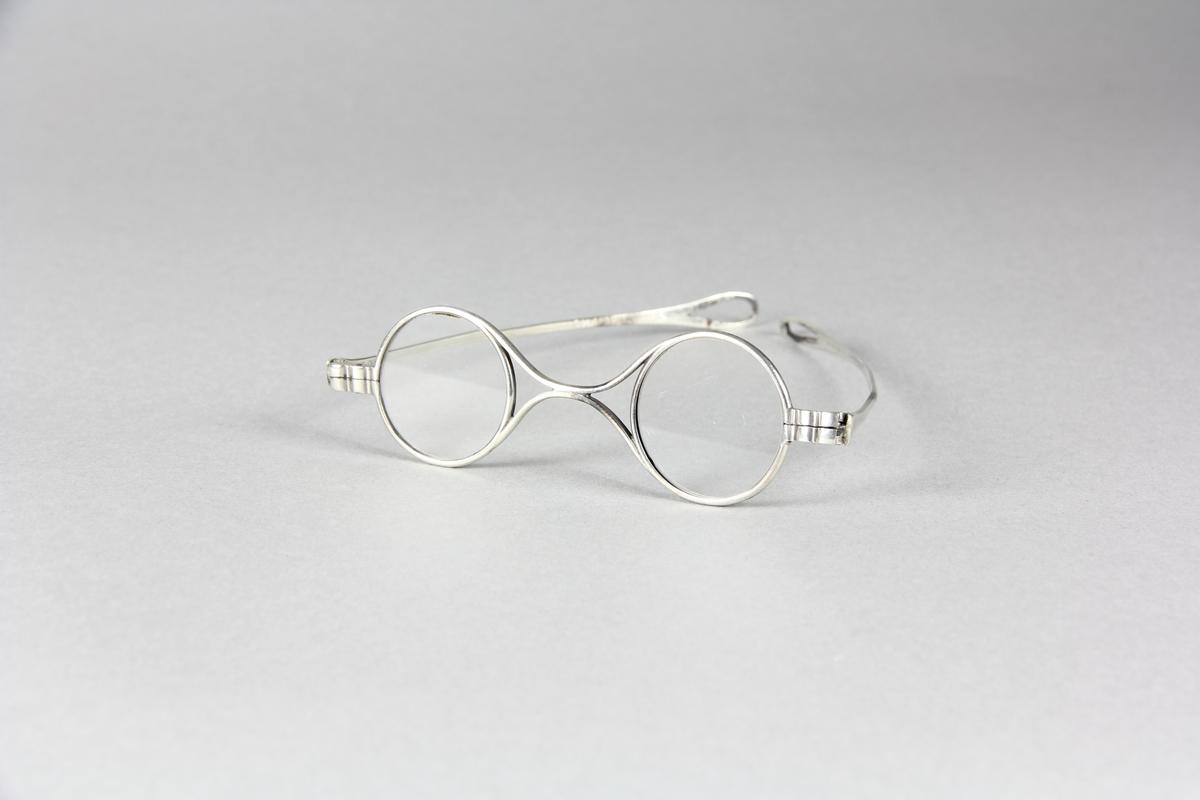 Glasögon, mindre glas och smala bågar av silver.  Två skalmar som utåt avslutas med droppformade öglor.