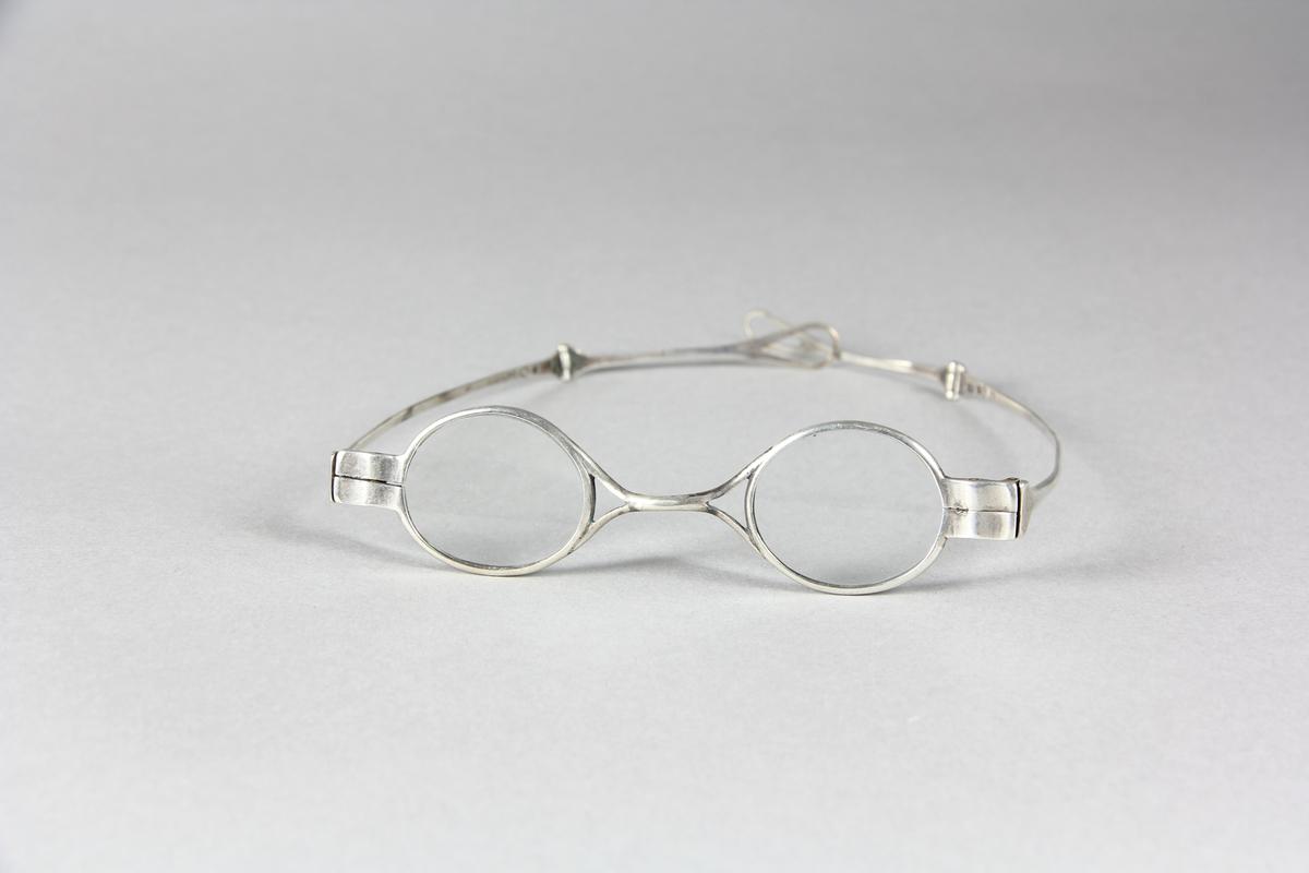 Glasögon, mindre glas och smala bågar av silver. Två ledade skalmar som utåt avslutas med droppformade öglor.