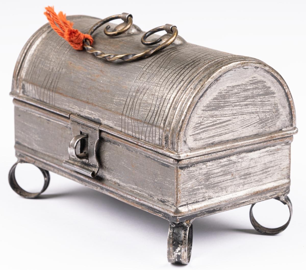 """Litet plåtskrin. I skrinet ligger en papperslapp med texten: """"Modell inlämnad av Fru Wilelund den 7/10 1937""""."""