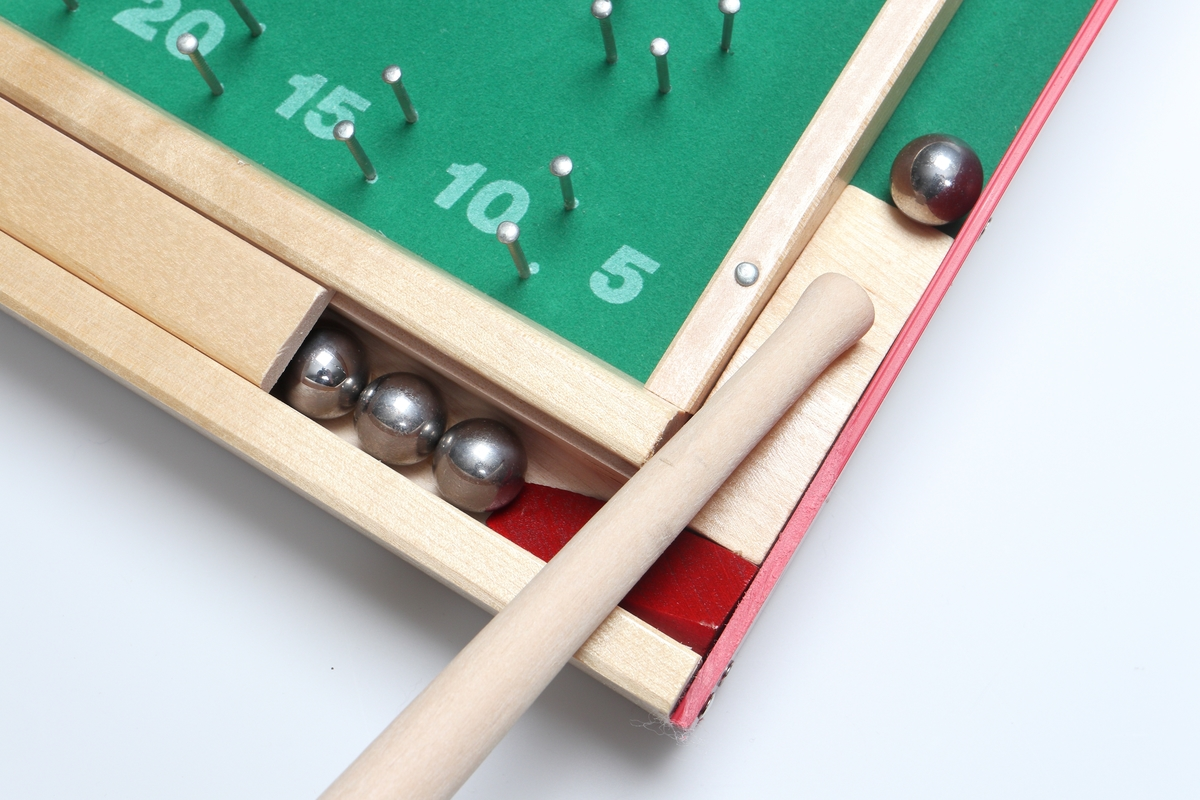 Fortunaspel.  Spelet är tillverkat av spånskiva rundad i ena änden och försedd med en påspikad sarg av böjt, rödmålat trä.  Skivan är klädd med grön bordsfilt som har blanka spikar islagna för markeringarna och dessutom försänkta blanka metallkapslar. Siffermarkeringarna är tryckta på.  Längst ned på spelet finns en låda med skjutlock innehållande tio st. metallkulor. Med spelet följer också en svarvad  kö och en träbit att fästa undertill, så att spelplanen får rätt lutning. På baksidan finns spelregler på engelska och svenska.
