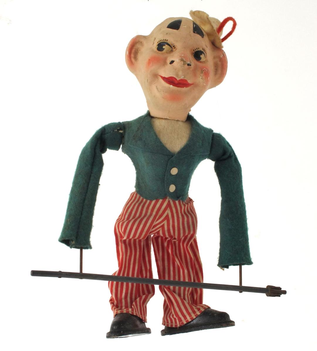 Klovnfigur, hode og bryst av pappmasje e.l. Grønn jakke og rødstripete bukser og hvit hatt.  Påmontert svingstang av metall. Sorte sydde sko.