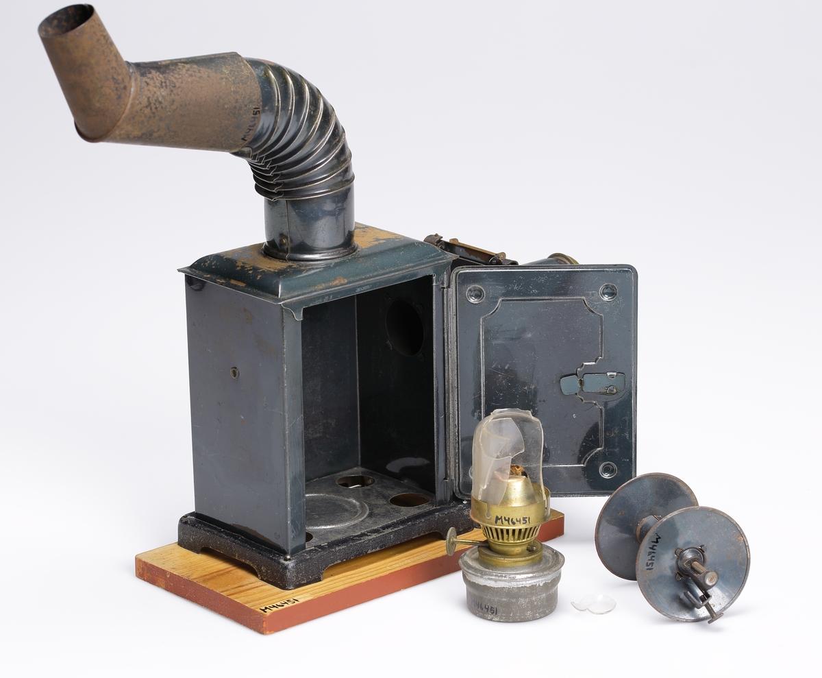 """Projektor för rörliga bilderm typ Laterna Magica. Den sitter monterad på en träplatta och består av ett lamphus tillverkat av blåanlöpt tunn pressad plåt. Framför detta finns lins, samt frammatningsmaekanik för filmen.  Filmen vevas fram genom en vev på högra sidan, den driver också slutare/klippare som går för linsen vid varje filmrutas slut. Ovanpå lamphuset sitter två rökhuvar bestående av ett 90 graders böjt rör med fläns samt däri ett instucket vinkelböjt koniskt rör som avslutning. Ljuskällan i projektorn består av en liten fotogenlampa med oljehus av förtent plåt. Lampan sätts in i lamphuset genom en gångjärnsförsedd dörr på projektorns högra sida.  Med projektorn finns också sex filmer tillverkade av cellulloid/nitrat. De är hopfogade och bildar ringar som sätts in i projektorn.  Alla filmerna har tecknade motiv som rör sig kontinuerligt. De har följande handling: 1. Brottare 2. Två pojkar på ett gungbräde 3. Man som dricker ur en flaska 4. Fem män som håller varsin ände av ett brandsegel 5. En man som travar tegel plus en medhjälpare 6. Tre män som står runt ett städ och slår på det samma. Apparatens tillverkare och tillverkningsår är okänt men förmodligen mellan 1925-1940. På driven och träplattan står: """"DRP Angemeldet"""". Förvaras i en skokartong."""