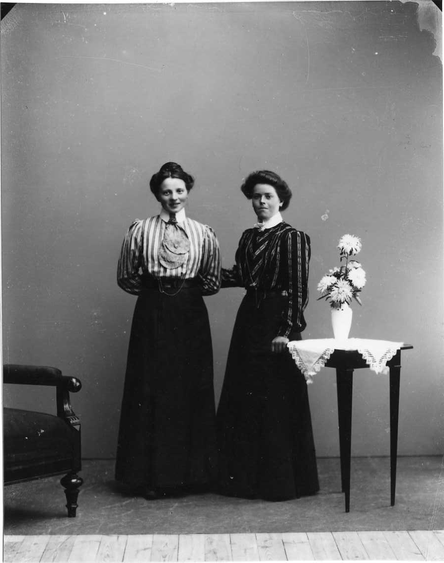 Gruppbild med två unga kvinnor i randig blus och lång mörk klänning. Kvinnan till höger är Jenny Johansson från Örserum.