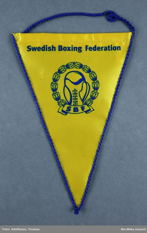 1 styck vimpel i gult med detaljer i blått. Med Swedish Boxing Federations emblem.   Längd 20 cm. Bredd 14cm.  2019-03-01 Cecilia Hammarlund-Larsson/Lena Kättström Höök