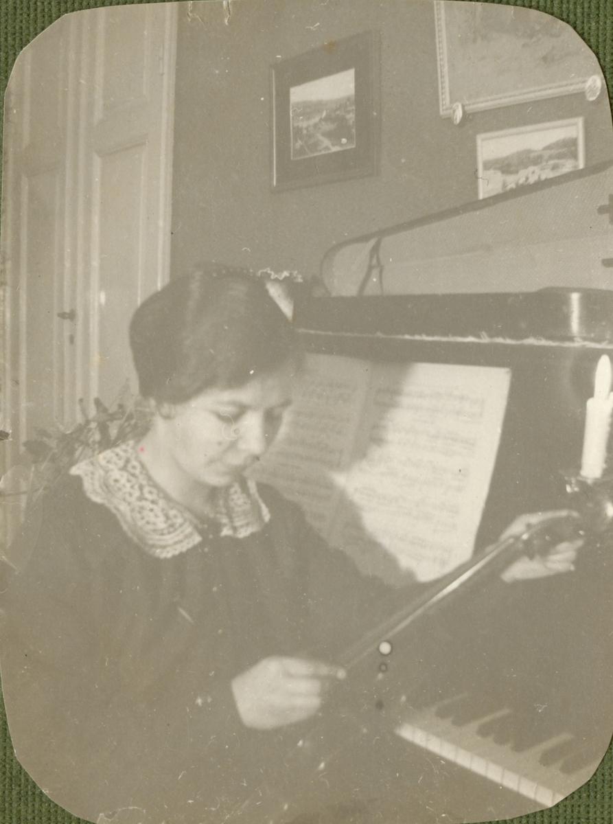 Porträtt av en kvinna vid piano.