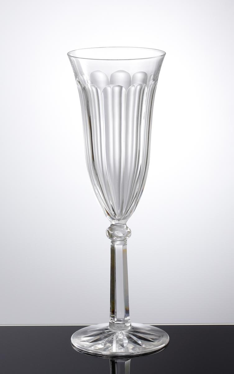 Champagneglas med slipade facetter på kupan. Slipat ben med kula, även den facettslipad. Skärslipad stjärna under foten.