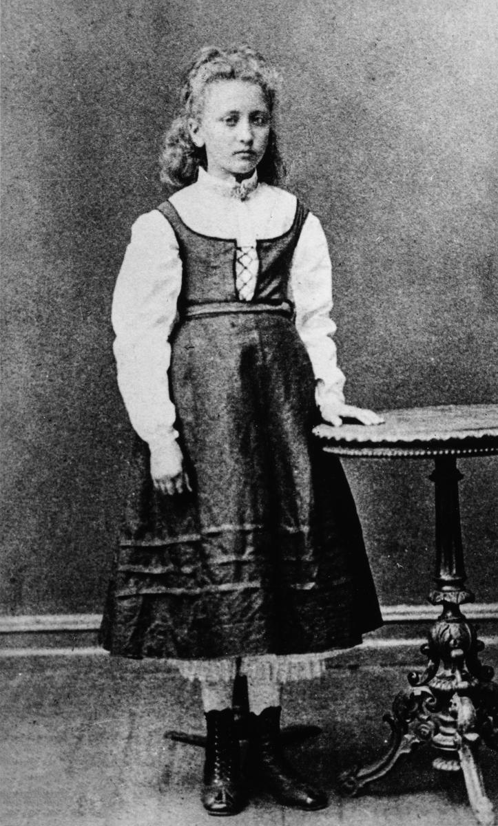 Barne portrett av Karen Hulda Bergersen, senere kjent som Hulda Garborg,  der hun er kledd for å gå på ball på Sælid i Vang.   Karen Hulda Garborg (født Bergersen 22. februar 1862, død 5. november 1934) var en norsk forfatter, kulturarbeider og oversetter. Hun er kjent for sitt engasjement for Det norske teater, folkevisedans og bunader. Hun giftet seg med Arne Garborg i 1887. Hulda var fra Stange i Hedmark. Faren drev storgården Såstad, men hadde store alkoholproblemer. Etter hvert flyttet moren ut, og tok med seg Hulda og hennes to eldre søstre til Hamar. Etter skilsmissen klarte moren så vidt å livnære seg og Hulda som sydame. Hulda vokste opp atskilt fra søstrene, og fikk også et anspent forhold til sin mor. Som ung jente flyttet Hulda til Kristiania, der hun ble opptatt av arbeiderbevegelsen og norsk nasjonsreising, blant annet målsaken.