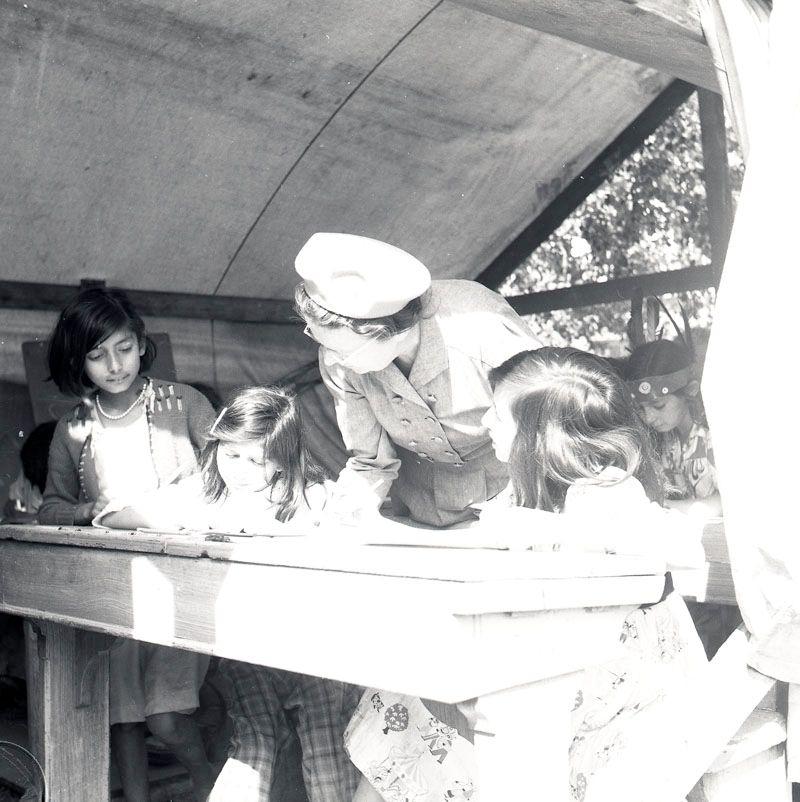 """Fotografiet är taget i juli 1952 i samband med skolundervisning i det romska lägret i Ekeby, ca 4 km väster om Eskilstuna. Lärarinnan som vanligtvis undervisade i Göteborg, var denna sommar där på uppdrag av Stiftelsen svensk zigenarmission för att lära barnen i lägret att läsa och skriva mellan 15 juli till 15 augusti. I en lärarrapport från september samma år har lärarinnan beskrivit sitt första möte med lägret i Ekeby med följande målande beskrivning: """"Redan när jag den 15 juli kom till lägret stod skoltältet färdigt placerat mellan två bostadsvagnar. Sex stycken av Eskilstuna stad kasserade skolbänkar fyllde upp skolrummet. På ena kortsidan var en likadan av Eskilstuna stad kasserad liten svart tavla uppspikad."""" Lärarinnan berättar i rapporten om undervisningen: """"På de små skolbänkarna satt elever av olika åldrar som besökte skolan varje dag. De barn som tillhörde skolpliktig ålder var sex till antalet och alla flickor. Fyra av dem hade inga kunskaper i läsning och skrivning."""" Även lägrets yngre barn besökte skoltältet då och då. Ofta inleddes dagen med att torka av bänkarna som blivit blöta av nattens regn. Tältduken var inte av en sådan kvalitet att det höll skyfall ute. Efter en månads undervisning kunde lärarinnan konstatera att de flesta av eleverna kunde läsa enkel läsebokstext och började lära sig att räkna.  Undervisningen störs ibland av oväntade händelser. Den 9 augusti fick lägrets medlemmar besked från Drätselkammaren i Eskilstuna om att deras kontrakt löpt ut och att de måste flytta innan skolan är över. Efter en annan polismästares bedömning blev flytten uppskjuten.   Lärarinnan sammanfattar sina upplevelser i Ekeby så här: """"Från första stund möttes jag av lägrets alla invånare med den största vänlighet. Föräldrarna var alltid ivriga då det gällde att sända sina barn till skolbänken. Vilka fördomar låter vi inte frodas omkring en minoritet, bara därför att den är olik oss""""."""