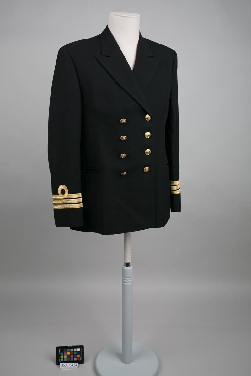 Orlogskaptein uniformjakke med 3 stk. gullbånd på erme og slag krage. Dobbelspent med til sammen 8 stk. knapper i gullfarge med motiv av anker.