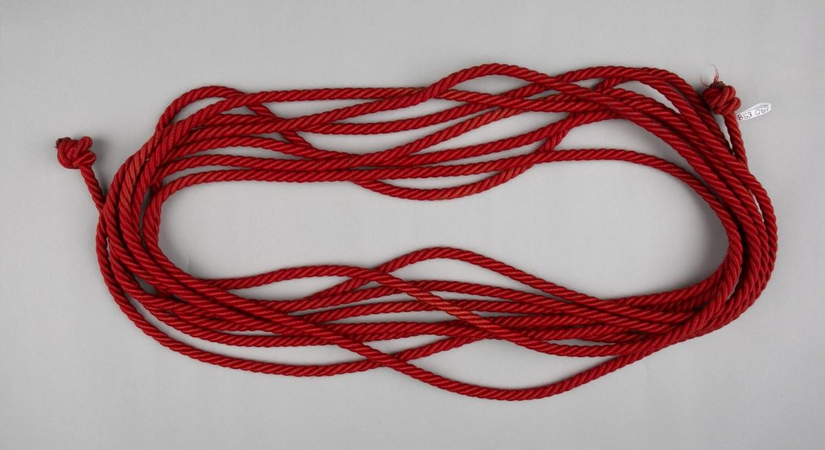 Fanesnor. Del til fane fra Bergen Losse- og Lastearbeiderforening. Rød fanesnor med knute i hver ende.