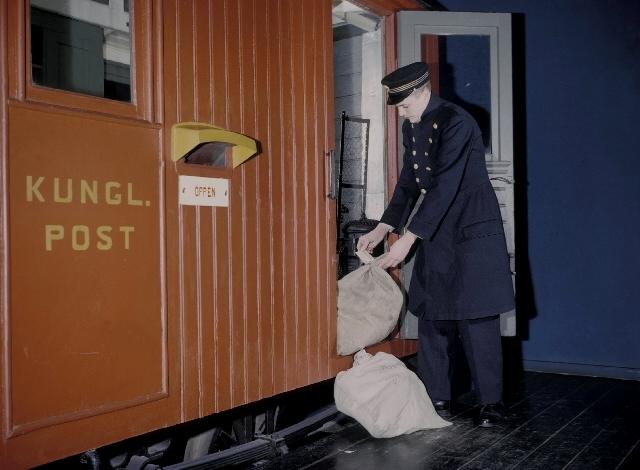 Seriebild M 25. Järnvägsvagn med postkupé från 1870-talet. Den hade trafikerat linjen Stenstorp - Hjo. I Postmuseums ägo sedan 1953. En järnvägspostiljon las-tar in postsäckar i kupén. I den arrangerade situationen agerar fotografbiträ-det Gunnar Svensson, Postmuseum.