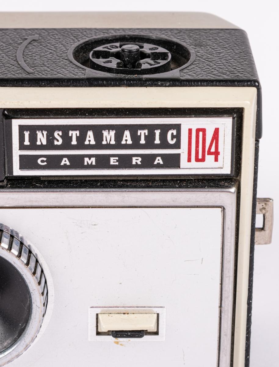 """Kamera, """"Instamatic 104"""". Av grå """"frostad"""" metall och svart, läderimiterad plast. Objektiv med räfflad kant. Sikthål överst i mitten. Uttag för blixtkub på ovansidan. I svart läderfodral med platt bärrem."""
