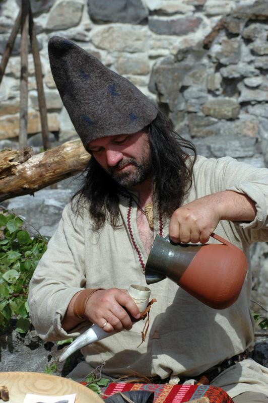 Mann med mørkt, langt hår, beige kjortel og spiss, grå filthatt står og heller drikke fra en terrakottamugge over i et drikkehorn. (Foto/Photo)
