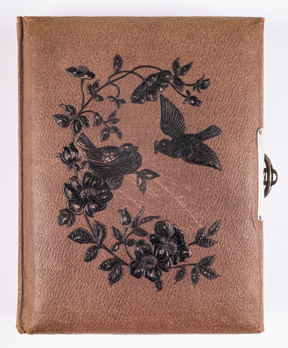 Fotoalbum för visitkort i brunt skinn. Pressat motiv i form av fåglar och blommor. Innehåller porträttfotografier.