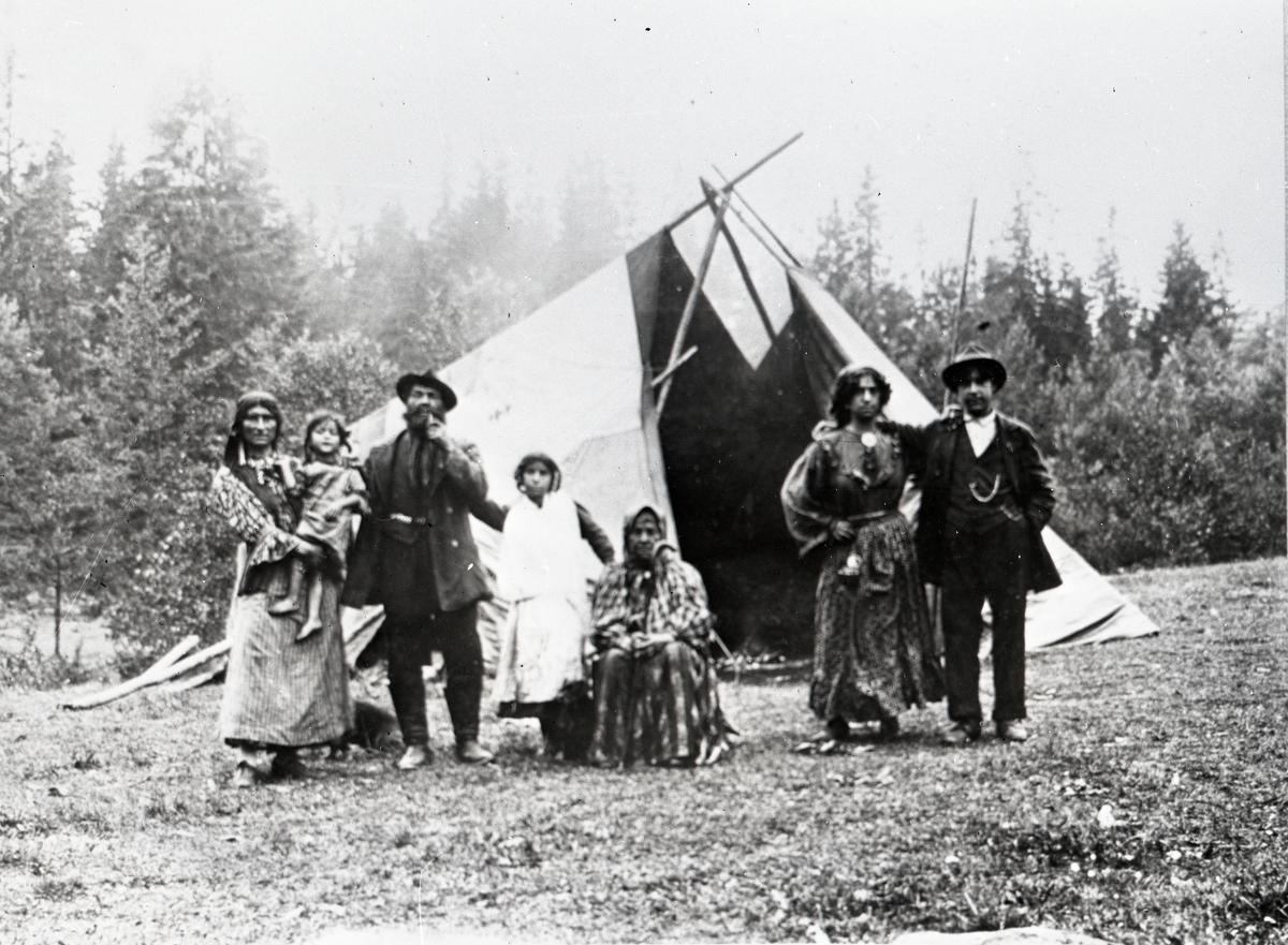 Framför ett tält står en familj uppställda för fotografering. Bildens ursprung är okänt, men är möjligen tagen under sent 1800- eller tidigt 1900-tal. Romer och resande har historiskt utsatts för hård diskriminering. År 1885 stiftades en lag i Sverige som gjorde det olagligt att vara arbetslös, egendomslös eller kringvandrande. Samtidigt började kommunerna under 1900-talets första årtionden att utfärda vistelseförbud, lägerslagningsförbud och näringsförbud för romer och resande. Trots detta saknade de flesta svenska romer fast bostad fram till 1960-talet. Boendestandarden bland svenska romer var under 1900-talets första hälft mycket varierande. Familjer som hade det bättre ställt kunde äga flera tält, medan fattigare familjer enbart hade ett tält. Man sov då där marken var minst lerig. Under 1940-talet förbättrades levnadsstandarden och flera svensk-romska familjer specialbeställde nu bostadsvagnar. Att inte behöva sova på marken utgjorde en avsevärd förbättring av livskvaliteten. Samtidigt var tältliknande konstruktioner enkla att montera ned då man ofta snabbt behövde bryta upp efter att lokala bråkmakare eller polis krävde detta.