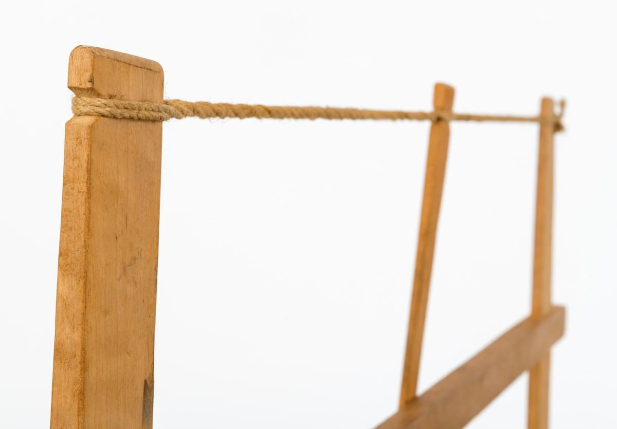 Såkalt grindsag, beregnet på snekkerarbeid. Det sentrale elementet i dette redskapet er en såkalt bom, ei 68 centimeter lang trestang med tverrsnitt 2,6 X 1,7 centimeter. Cirka 4 centimeter fra ytterendene av denne bommen er det rektangulære hull for sagarmene, som er montert noenlunde vinkelrett på bommen. Sagarmene er 34 centimeter høye. I de nedre. avrundede endene av disse komponentene er det hull for endetappene til de dreide handtakene som brukes til å justere arbeidsvinkelen på sagbladet. Denne saga har et drøyt 6 millimeter bredt blad med om lag 2 millimeter høye støtstilte tenner. Mellom de øvre endene av sagarmene er det viklet ei snor - et sagtrekk - som tvinnes ved hjelp av en 18,7 centimeter lang pinne, omtrent på midten. Ved å rotere denne pinnen tvinnes snora, slik at den blir strammere. Når de øvre endene av sagarmene på denne måten trekkes mot hverandre, trekkes de nedre endene fra hverandre, så sagbladet strekkes. Bommen i denne grindsaga ser ut til være lagd av kvistfritt furuvirke, de øvrige trekomponentene later til å være av bjørk.