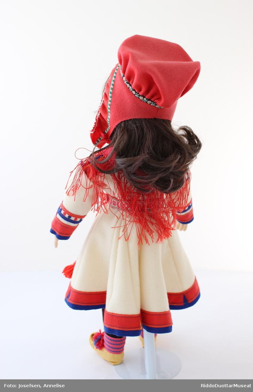 Dukke med tekstil ansikt og hender. Sort syntetisk parykk. Dukken er ikledd kvinnekofte fra Kokelv, kvinnelue fra Karasjok, rødt silkesjal, maskinvevd belte, sort strikket strømper/bukser, komagbånd med dusker, kommager og sølje på sjalet. Dukken står oppreist på et stativ.