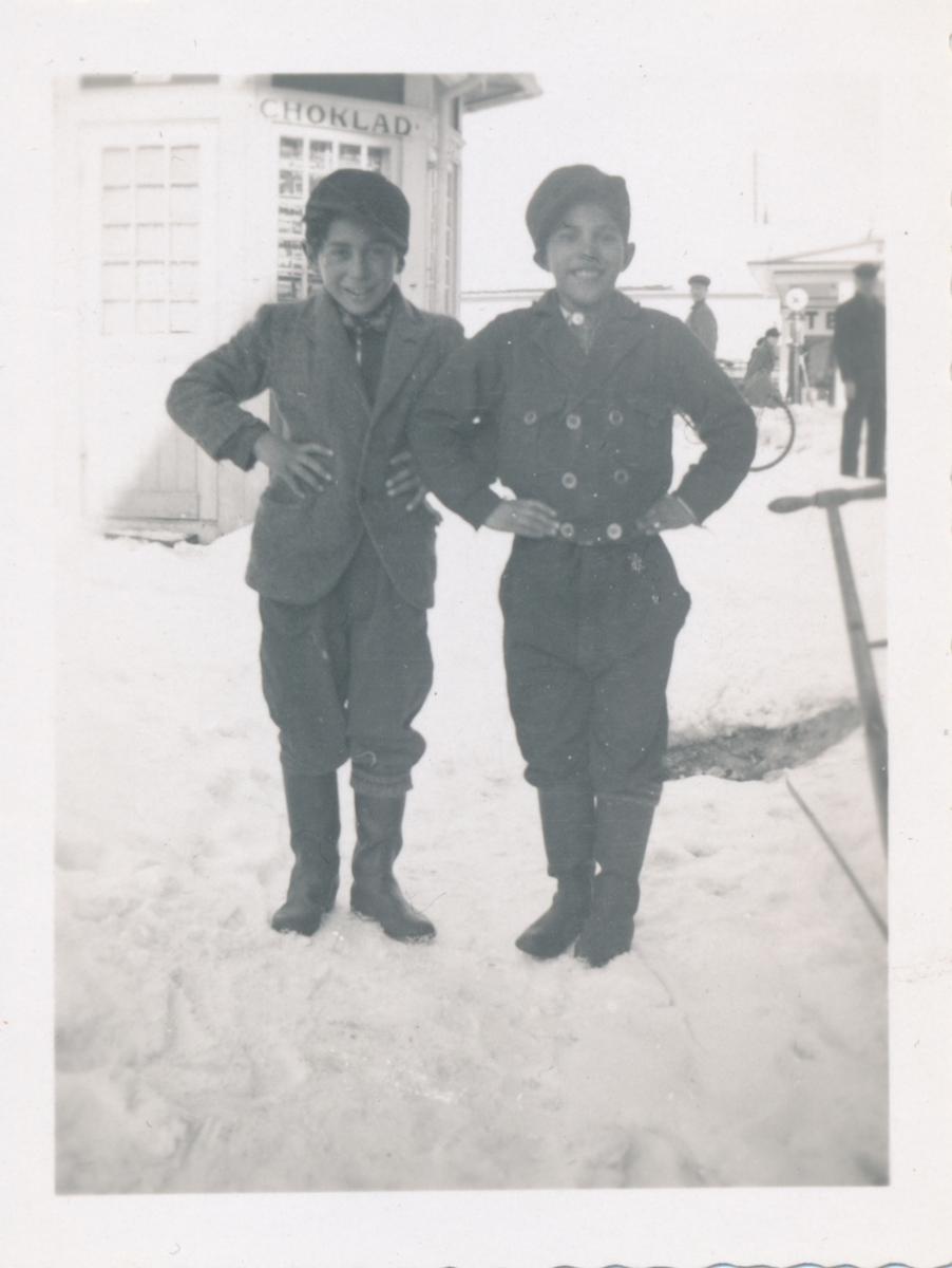 Med händerna i sidorna står två pojkar och ler mot kameran.