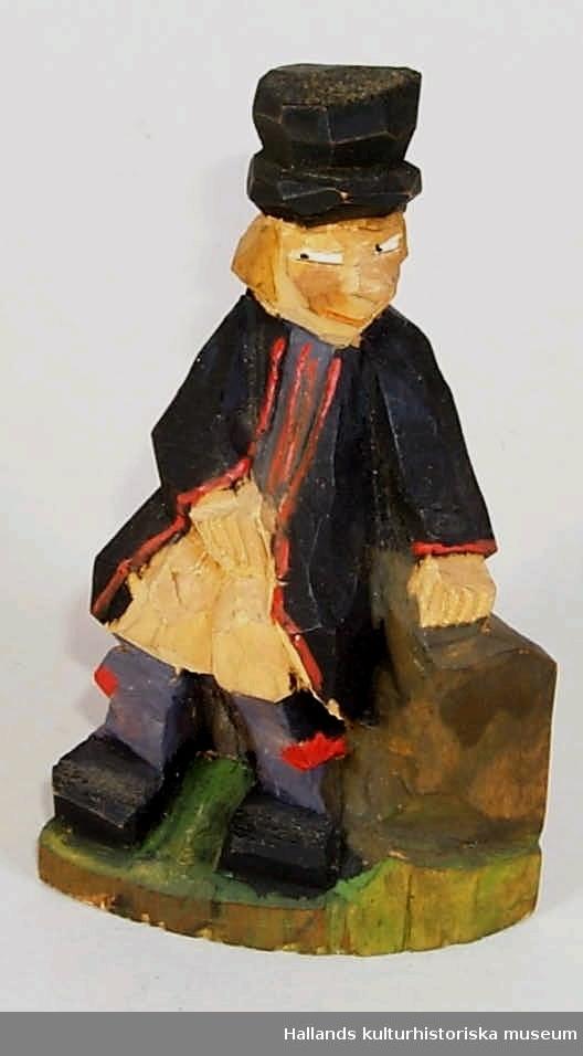 """Snidad mansfigur föreställande dalmas-klädd person sittande på sten (eller stubbe). Leende i mjugg. Målad i svart, rött, brunt och grönt. Märkning: """"H Bl. nk. Rättvik 12:- L.B"""", aningen svårtytt inristat och skrivet med bläck (?) undertill."""
