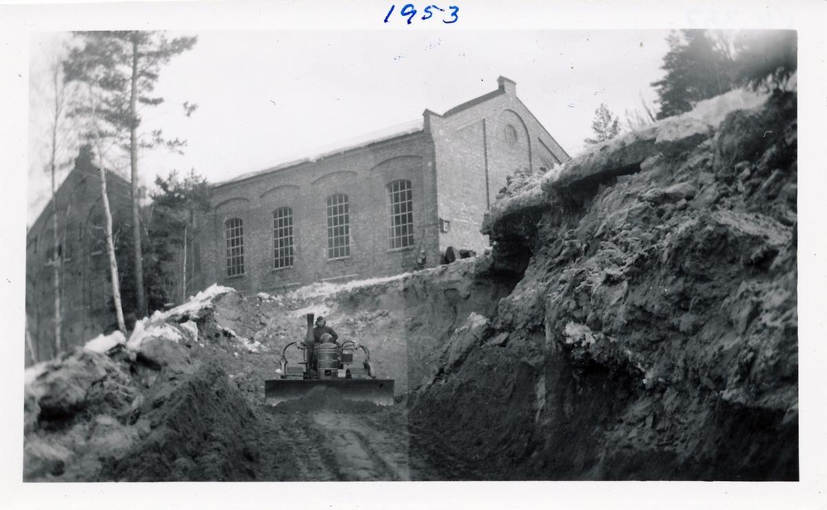 Tomt graves ut for å bygge kraftstasjonen Kistefoss II ved siden av det eldste tresliperiet. Mann på bulldoser jobber med jordmassene.