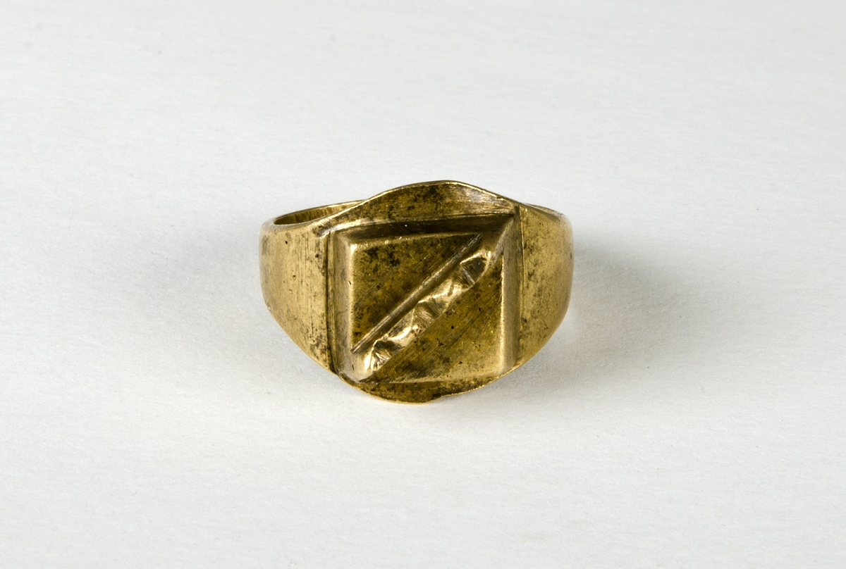 """Fingerring av metall, sannolikt mässing. Lödning i """"bakkant"""". Dekoren är en kvadrat med en upphöjd """"kam"""" med fyra taggar. En trolig datering är historisk tid."""