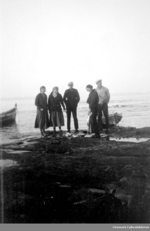 Tre damer og to menn ved fjæra i Salttjern, to båter i bakgrunn.