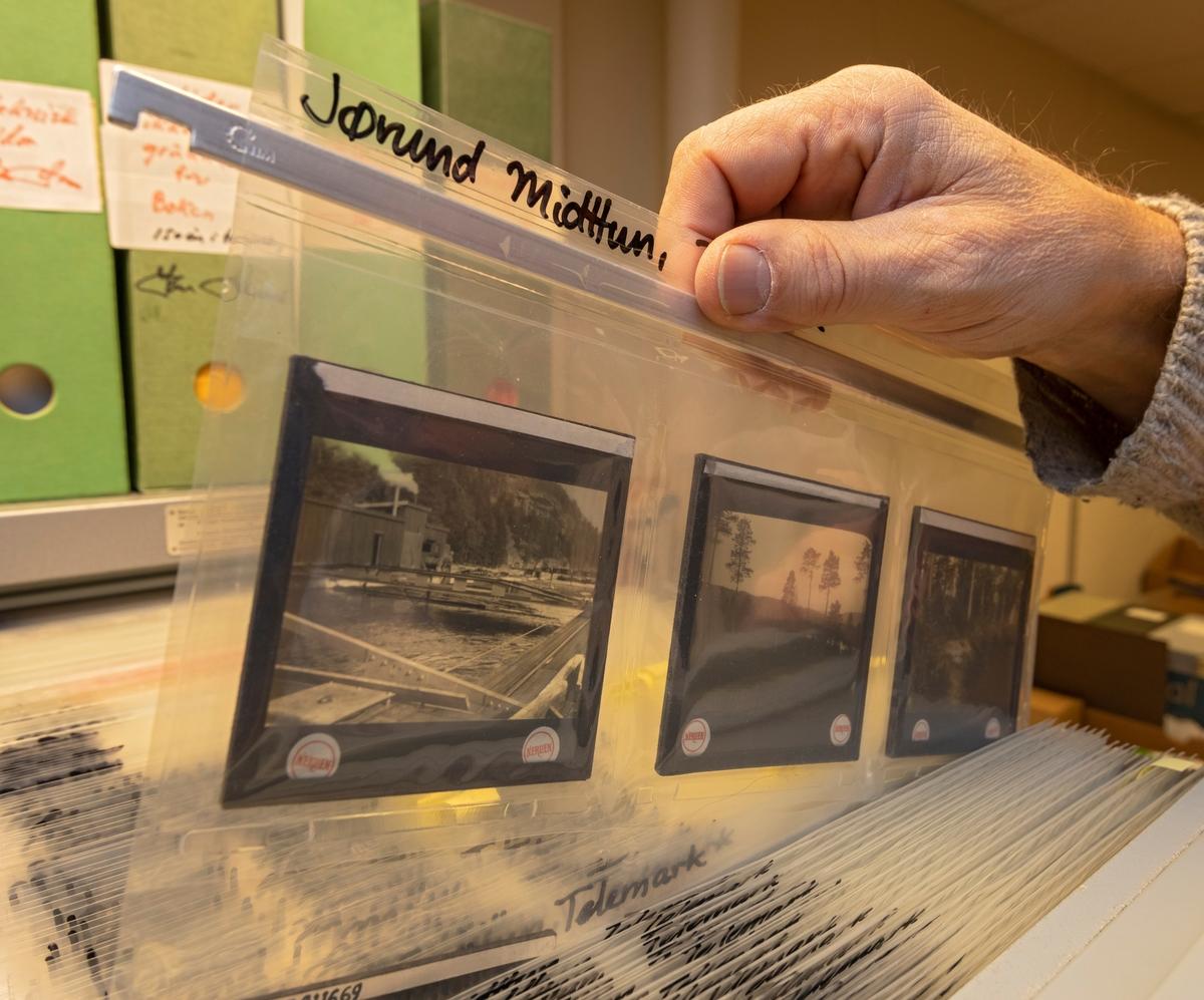 Fra et av Anno Norsk skogmuseums fotoarkiv, som man da dette fotografiet ble tatt, i 2020, antok omfattet cirka 300 000 opptak. Mange av fotografiene er tatt av museets egne fotografer, OT Ljøstad (1973-2013) og Bård Løken (2014-), men museet har også fotosamlinger etter privatpersoner, organisasjoner og bedrifter med tilknytning til museets tematiske arbeidsfelt. Fotografiene registreres i databaseprogrammet «Primus», og materialet publiseres (med tekstinformasjon og digitale gjengivelser av motivene) via nettstedet DigitaltMuseum. Da dette fotografiet ble tatt var om lag 40 000 av Skogmuseets fotografier registrerte i Primus-databasen, men bare om lag 25 000 av disse var presentert på Digitalt museum. Den forholdsvis store differensen skyldes dels etterslep i digitaliseringsarbeidet (mange av Primus-postene mangler digitale fotovedlegg), dels at informasjonen om mange av opptakene er meget tynn og manglefull. Museet arbeider kontinuerlig med å styrke kvaliteten på eksisterende Primus-poster og sørge for at stadig flere fotografier blir tilgjengeliggjort via nettstedet DigitaltMuseum. Dette fotografiet viser noen av svart-hvitt-diasene etter Jørund Midttun (1887-1969), som var fylkesskogsjef i Telemark og en dyktig amatørfotograf.