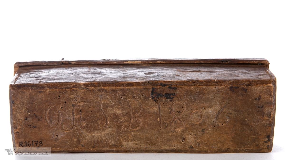 Rektangulær treeske hulet ut av av en trestokk, som er inndelt i tre innvendige rom. Utskåret lokk med kanter og låsemekanisme.