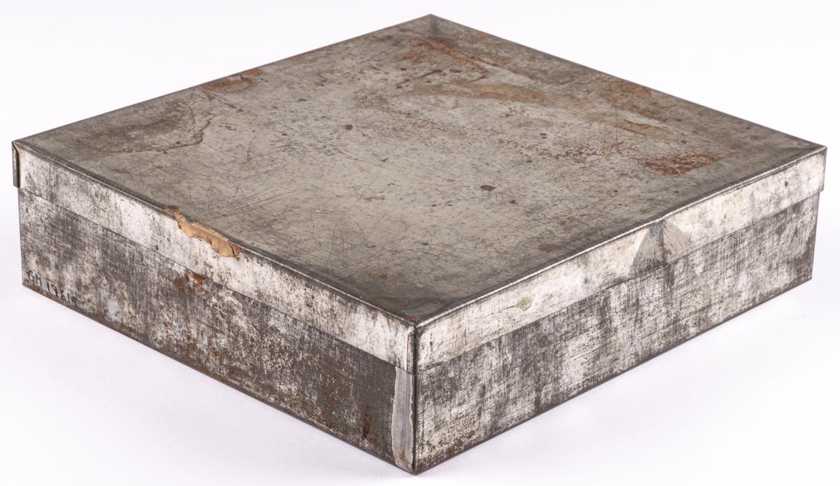 Mjölkpoletter av mässing förvarade i bleckplåtslåda. Text på de rektangulara brickorna: FORSBACKA JERNVERKS AKTIEBOLAG 1Lit. SKUMMJÖLK. Poletternas mått: 21 x 32 mm. Lådan 230x215 mm.