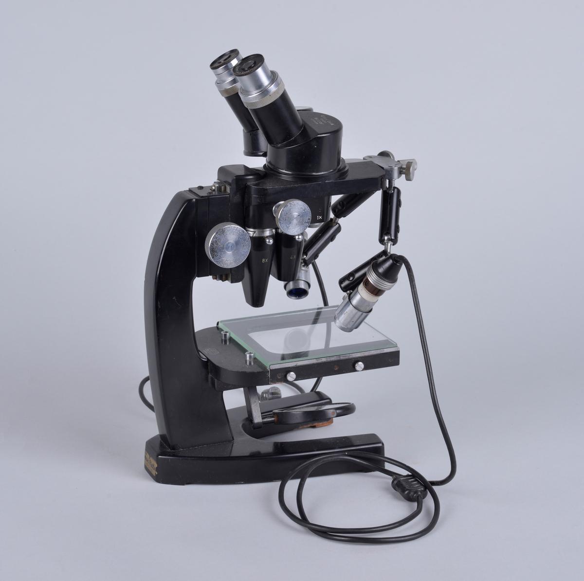 Binokulært mikroskop, har to okularer for bruk med begge øyne. Apparatet er produsert i Tyskeland og brukt av Vetrinærinstituttets fagfolk.   Chassiet er muligens laget i stål, svartlakkert.