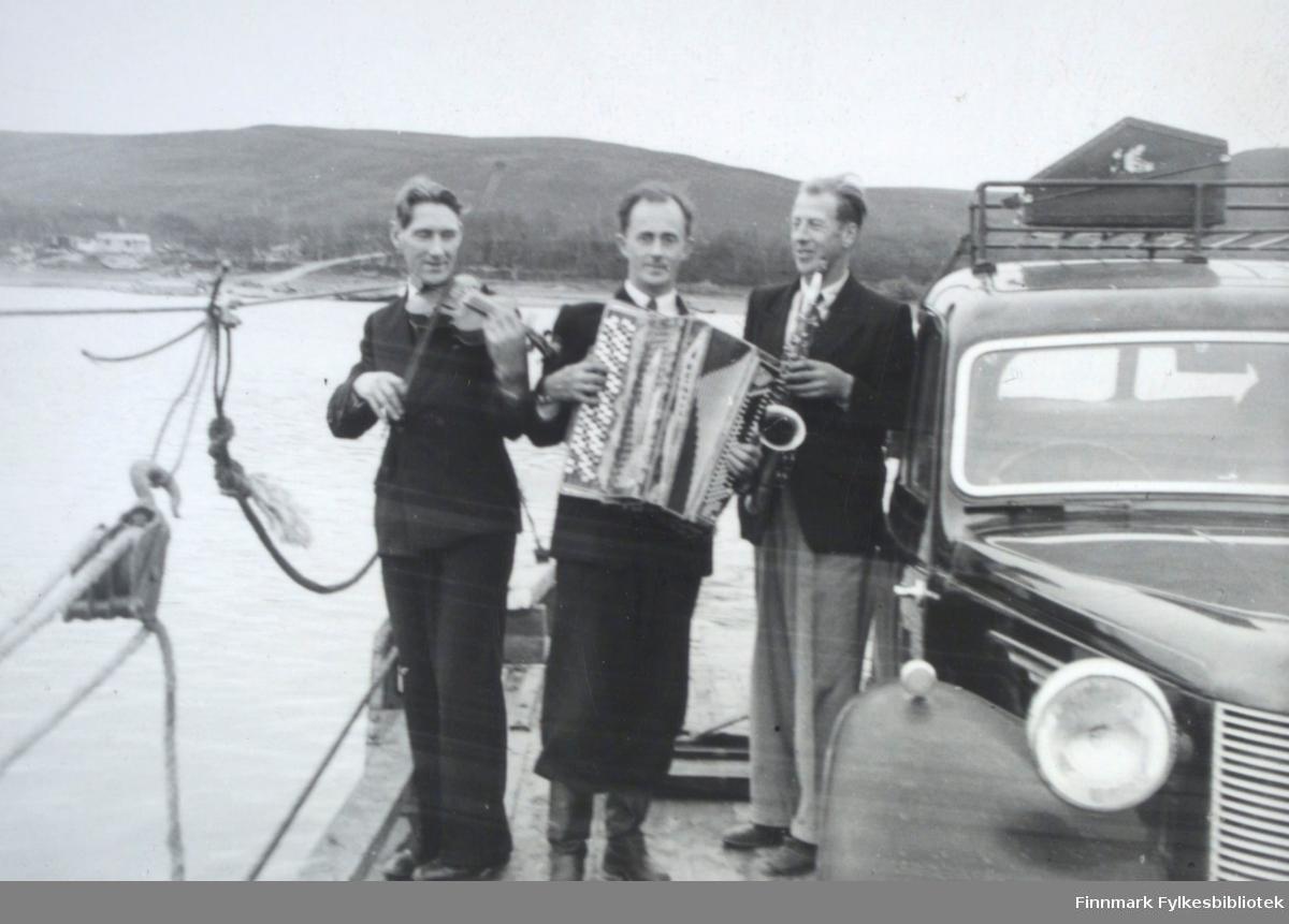 Fra venstre: Ole Johnsen (fiolin), Ivar Sælø (trekkspill) og Edmund Jankila (saxofon). Et sted langs Tanaelva med ferge, muligens i Seida, på 1950-tallet. Ivar Sæløs bil Austin A10 til høyre.