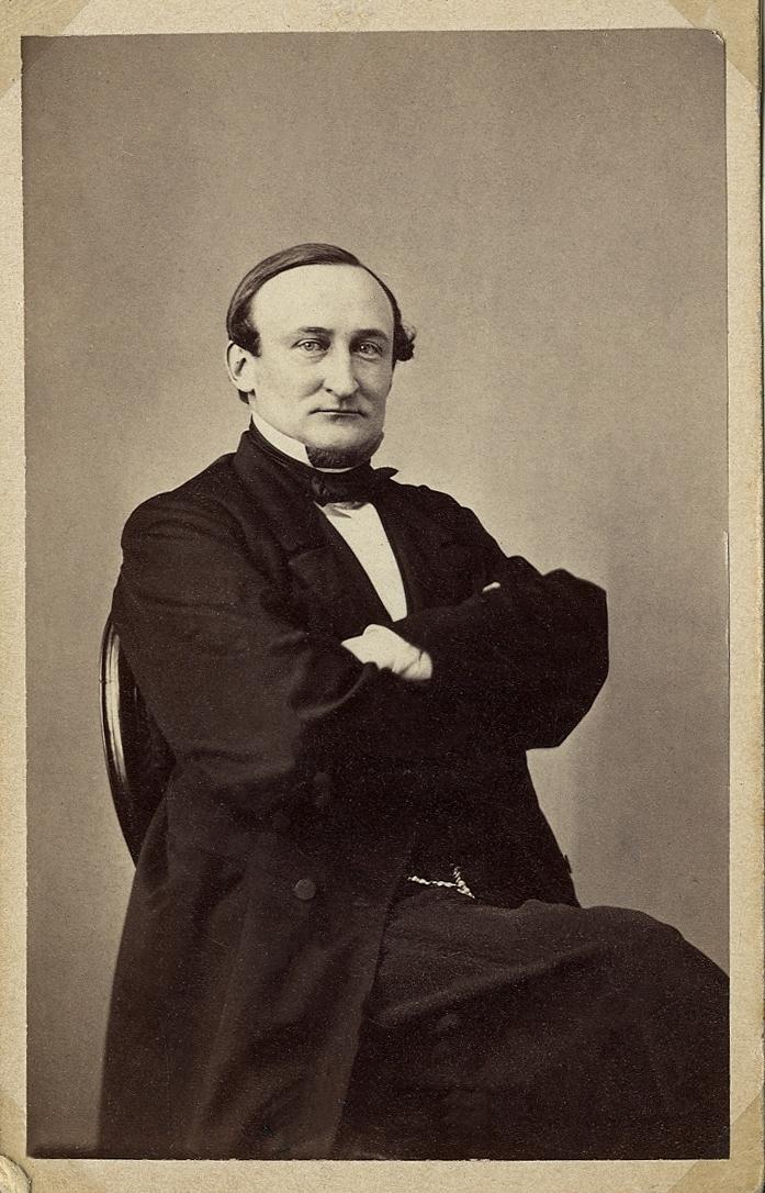 Foto av en man i bonjour med väst, stärkkrage och fluga, Han sitter på en stol med armarna i kors. Knäbild, halvprofil. Ateljéfoto.