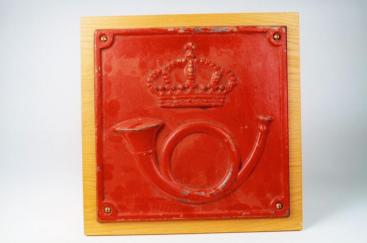Rødmalt postskilt med gulmalt postemblem og kant. Med krone uten løve.