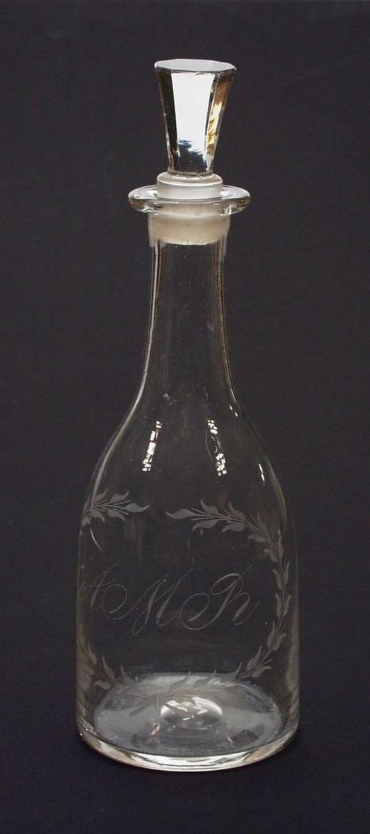 Vannkaraffel i klart glass med gravert monogram i en blomsterkrans. Korken er slipt.