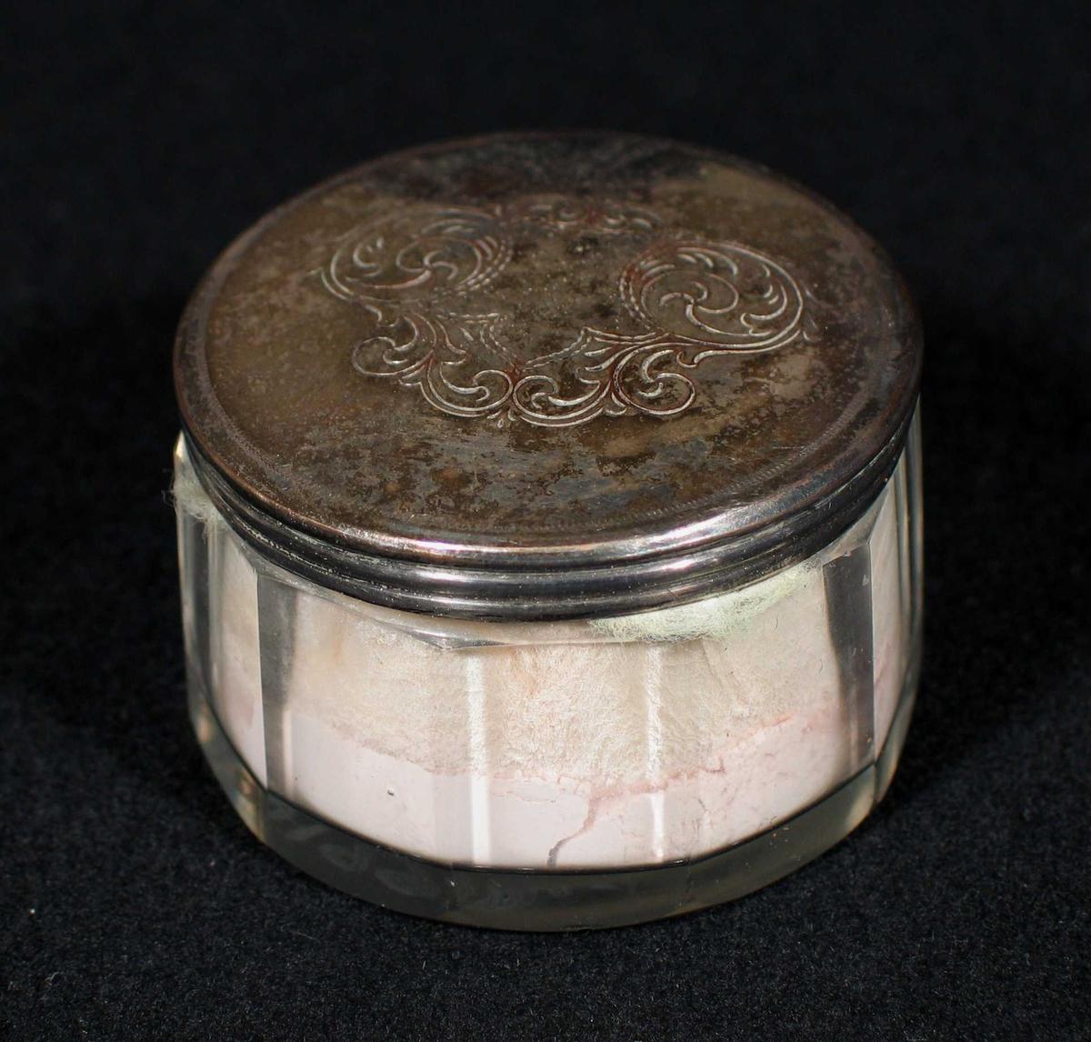 Glasskrukke med lokk i sølv. Gravert akantusmotiv på lokket. Inneholder rosa pudder