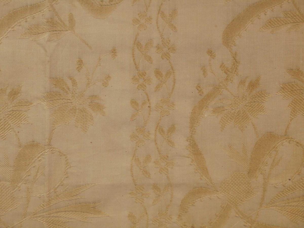 I øverste kant rustmerker og hull etter feste til rullen. Mønster: Vertikalt mønster. Bord 1: To tette bølgete linjer med kløverblad og firbladet blomst. Bord 2: Bred bord med stengler, blomster og blad. En rapport: Br.23 cm. En rapport: h. 45.