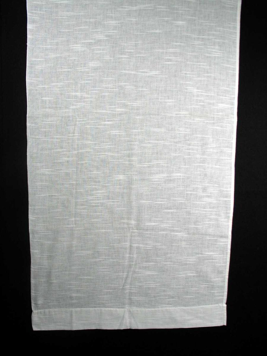 Hvit gardinlengde, faldet med maskin. Varierende tykkelse på tråden i innslaget gir stripeeffekt og struktur.