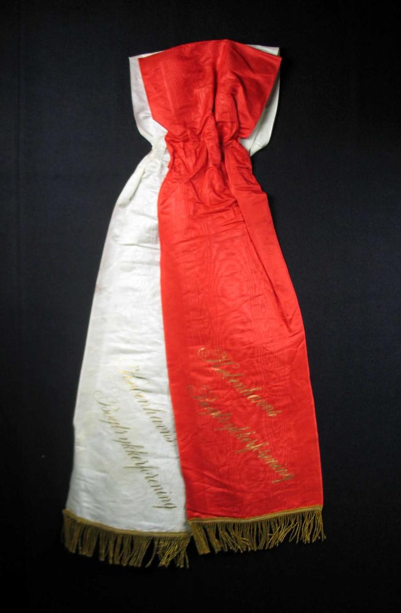 Begravelsessløyfe i hvit og rød silke med gullfrynser.