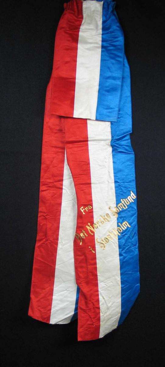 Begravelsessløyfe i blå, hvit og rød silke med tekst i gull.