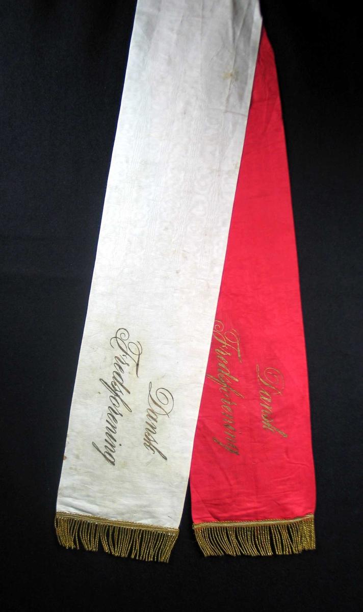 Begravelsessløyfe i rød og hvit silke med tekst og frynser i gull.