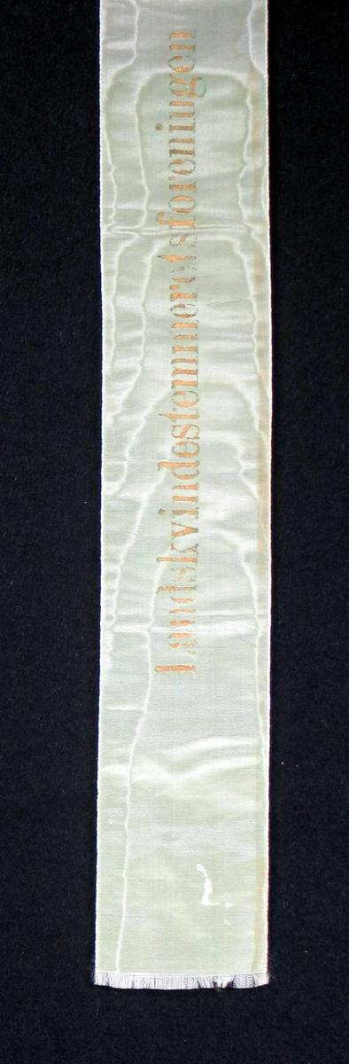 Begravelsessløyfe i hvit silke med tekst i gull.