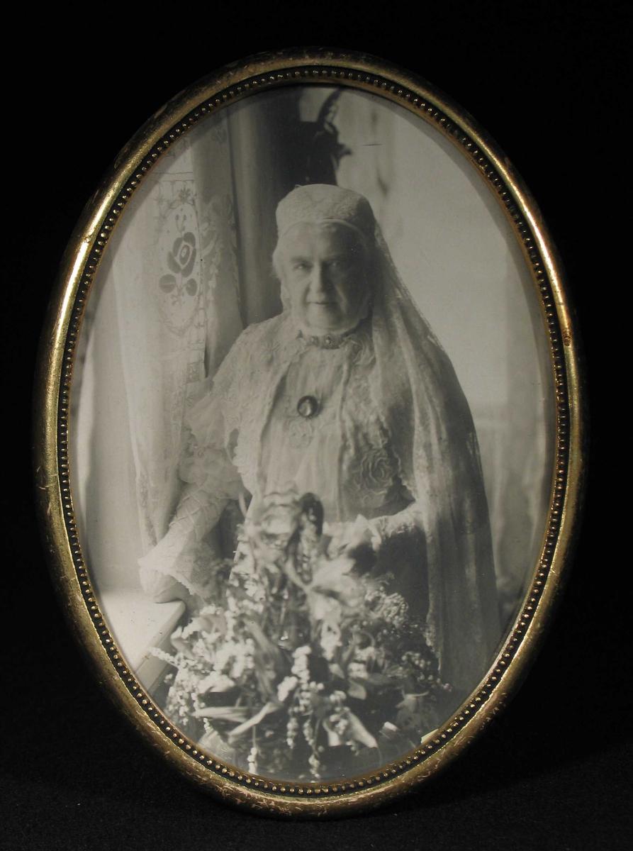 Eldre kvinne i hvit lang kjole stående ved et vindu med blomster i hånden.