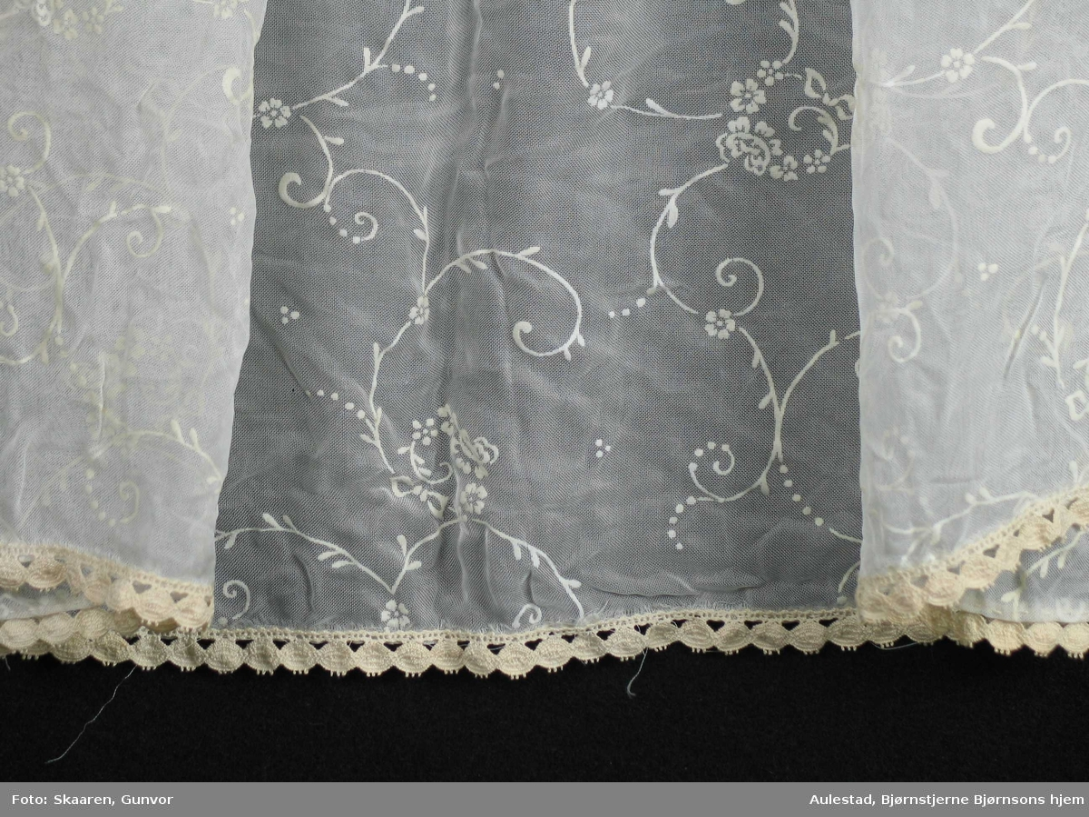 Hvitt tynt gjennsomsiktig stoff med flosstrykt blomsterdekor. Nederst en påtråklet smal blondekant. Håndfaldet i sidene og øverst en tråklet løpegang.