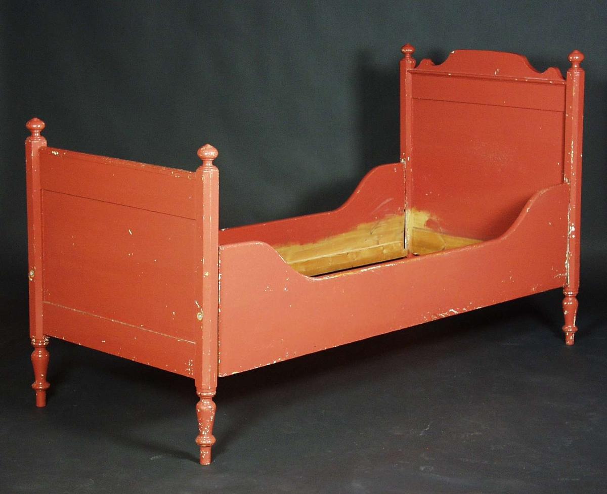 En rød seng i furu. Hodegjerdet har profilerte og opphevet midtparti øverst. Fotgjerdet er helt rett.  Stolpene på hode-og fotgjerde har dreide kuler på toppen. Vangene er lavere på midten.