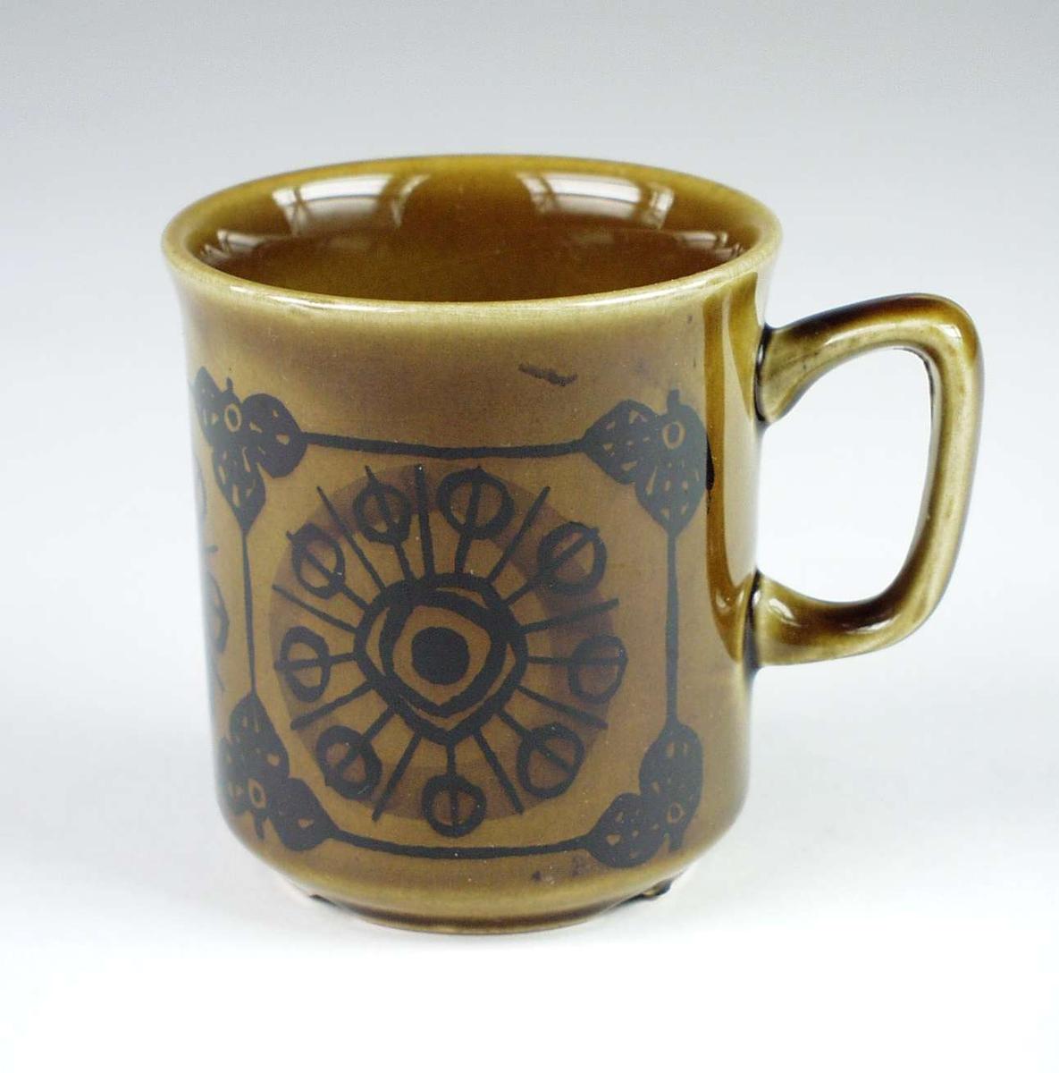 Syv brune kaffekopper i keramikk med mørk brun dekor. Serviset består ellers av elleve skåler og tolv asjetter.