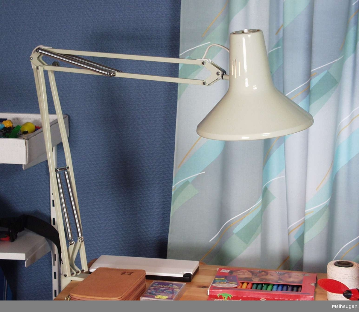 Grålakkert skrivebordslampe i metall med justerbar arm.