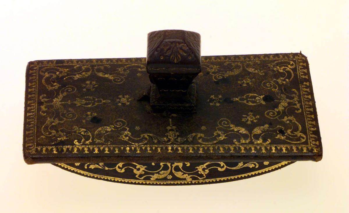Trekkpapirholder med buet, dekorert underside til å feste trekkpapiret på. Holderen er trukket med lær som har preget, forgylt dekor.